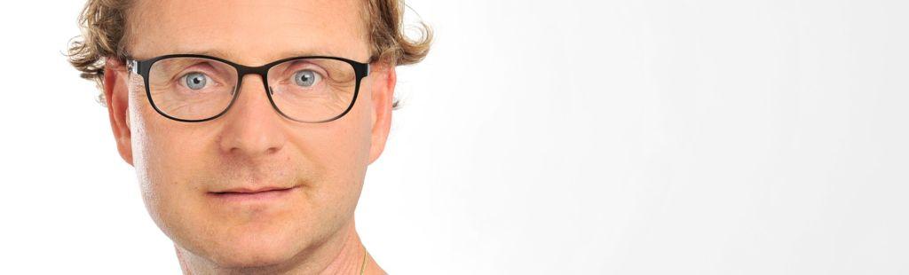 Foto Ralf Käppler mit Brille schauend.